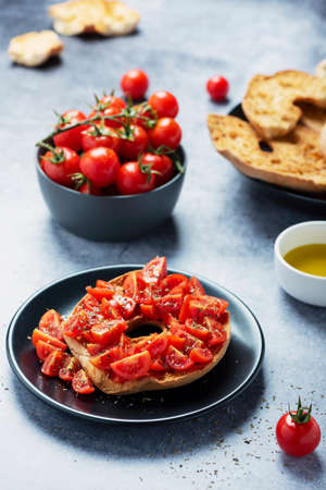 Concept of Italian food. Friselle with tomato, oil and origano. Closeup image with selective focus