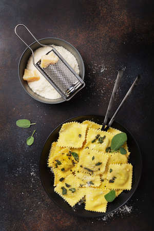 Top down view of a traditional Italian ravioli with butter, sage and cheese on a dark background. Concept of Italian food with copy space