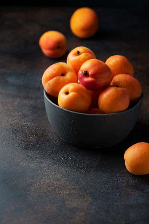 Concept of healthy vegan food with sweet apricots in a dark background, selective focus image Фото со стока