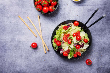 Concept of healthy vegan food. Salad with cucumber, tomato, green salad and chicory Фото со стока