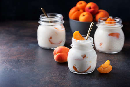Sweet healthy yogurt with apricots on the dark table, selective focus image