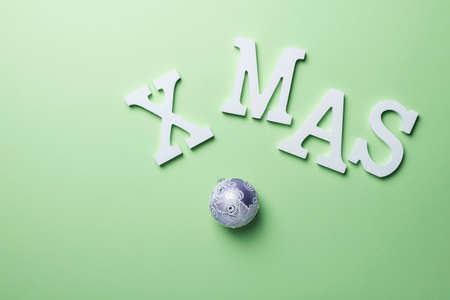 Christmas gift card with white letters on the green background. Holiday concept, top down view with copy space for text