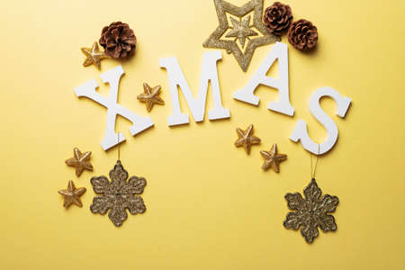 Christmas card with letters and Christmas decoration on the yellow background. Christmas concept, top down view Фото со стока