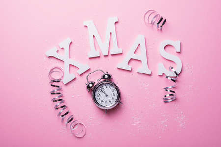 Christmas card with letters and clock on the pink background. Christmas concept, top down view Фото со стока