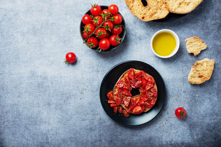 Concept of Italian food. Friselle with tomato, oil and origano. Top down view with copy space