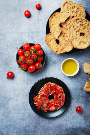Concept of Italian food. Friselle with tomato, oil and oregano. Top down view with copy space