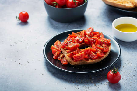 Concept of Italian food. Friselle with tomato, oil and oregano. Closeup image with selective focus