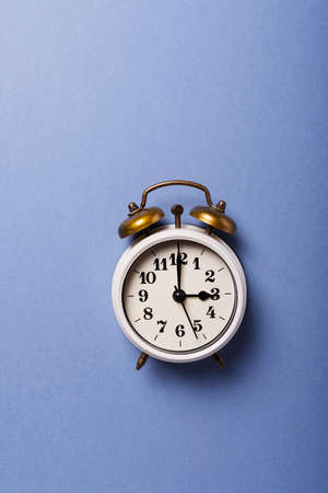 Concept of Daylight saving time. Retro clock on the blue background. Top down view with copy space Zdjęcie Seryjne