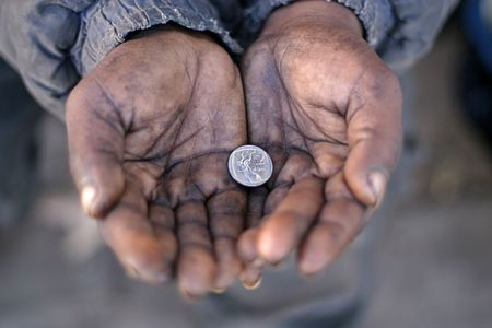 A Gipsys hands holding a silver coin Stock Photo