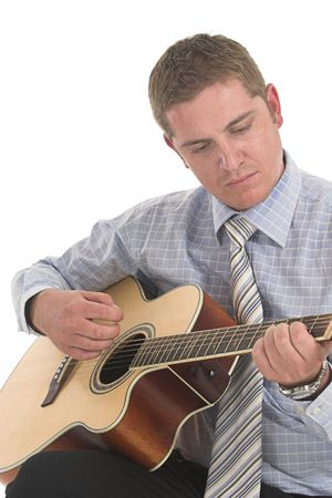 Man dressed in work outfit playing his wooden guitar photo