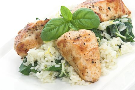 Chicken and rice with spinich and lemon toped with basil leaves