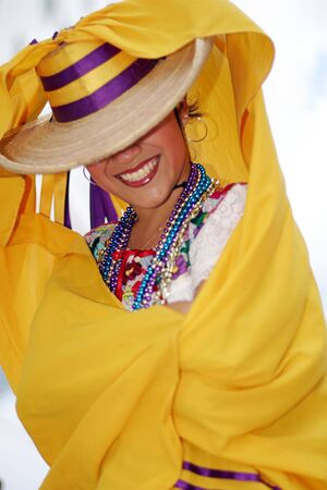 folk dancing: Pretty mexican dancer covering her face with a hat