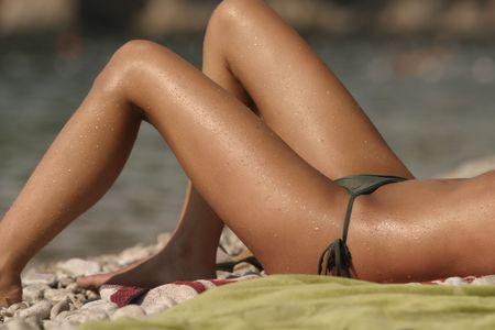 Dark skinned woman sunbathing on a pebble beach