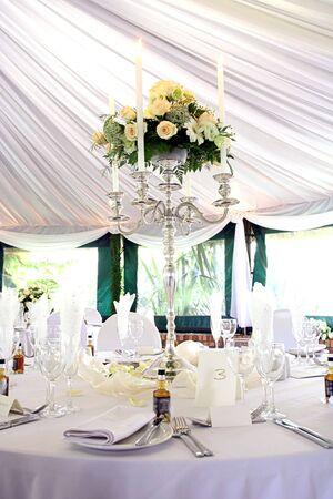 catered: Dinner table setting at a banquet with roses on a chandelier 2