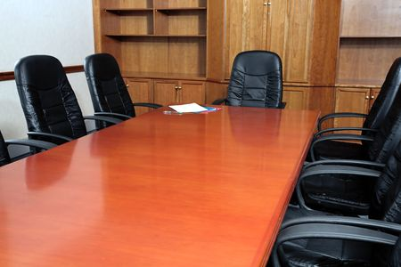 Black leather chairs around a boardroom table with files on the end