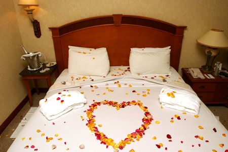 topped: Honeymoon bed topped with rose petals