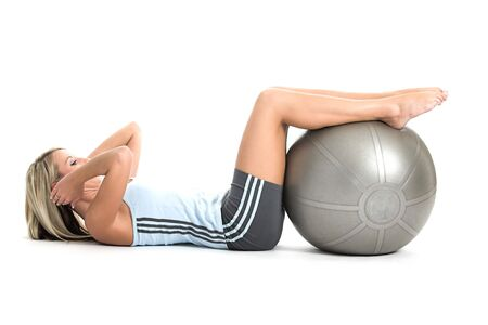 Blond woman in gym outfit excercising with a pilates ball