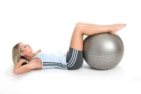Blond woman in gym outfit excercising with a pilates ball photo