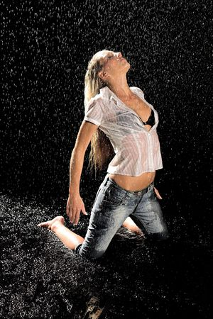Woman sitting on her knees in the rain photo