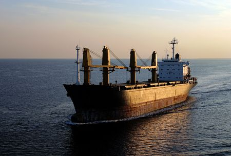 Cargo ship cruising the seven seas at sunset