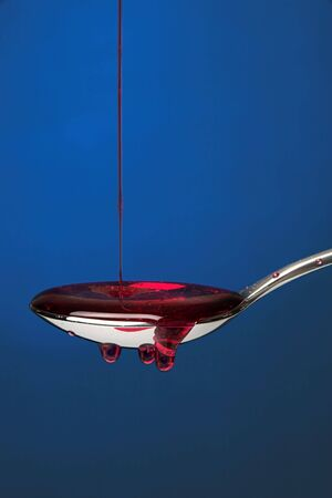 Spoon full of cough medicine over a blue backdrop 3 Stock Photo - 876080