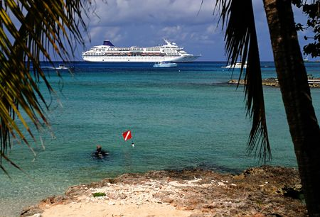 cruis: A Diver in the shallow water on an island with a cruis liner in the distance