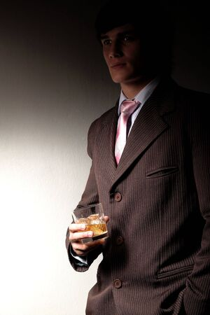 Model dressed in business suit with a glass of whiskey in his hand Stock Photo - 876098