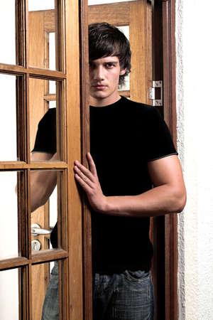 young man standing: Giovane uomo in piedi nella porta  Archivio Fotografico