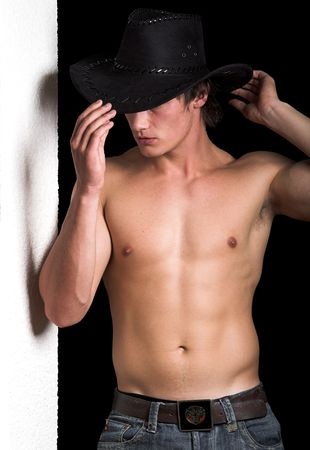 Shirtless cowboy leaning against a white wall 5
