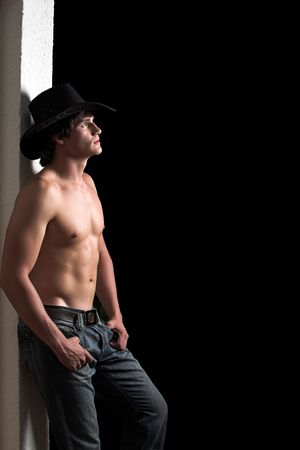 Shirtless cowboy leaning against a white wall 2 Stock Photo