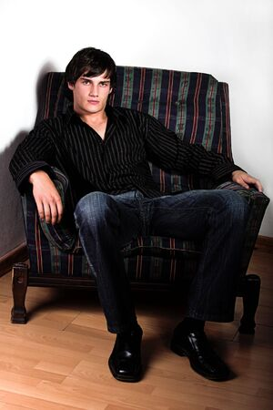 young male model: Los chicos modelo sentado en una silla de color