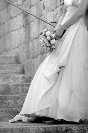 Black and white photo of a bride leaning against a wall holding her bouquet. photo