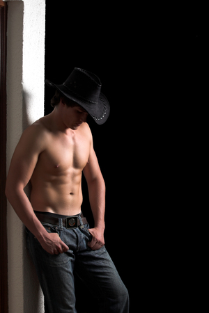 Shirtless cowboy leaning against a white wall Stock Photo