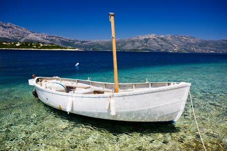 fishing scene: White fishing boat with a wooden mast docked in the beautiful clear waters of the mediterranean.