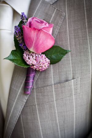 Pink rose boutonniere pinned to a grooms jacket.