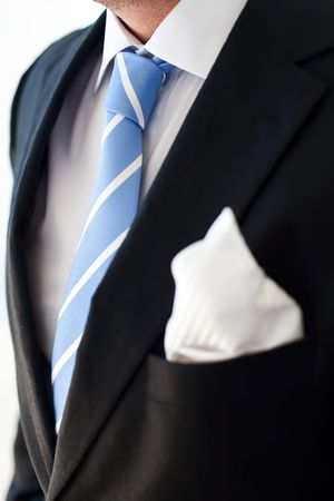 Groom wearing dark suit and a blue tie.