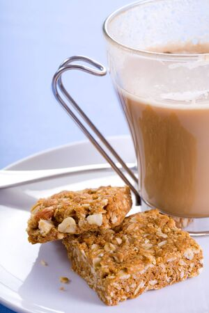 Nice hot cup of coffee in a see through cup with some healthy biscuits. photo