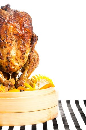 veg: Upright grilled chicken in a bamboo steamer filled with fresh veg. Stock Photo