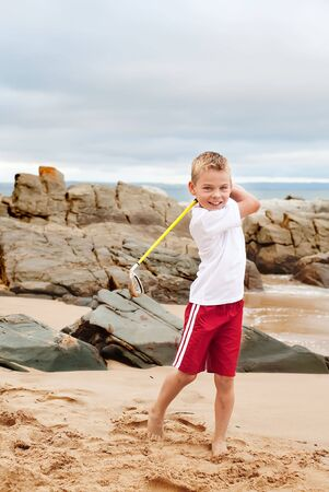 Happy young boy swinging his golf club on the beach. photo