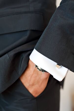 cuff links: Close-up of a mans hand in his suit pocket wearing a watch and a cuff-link on in shirt.