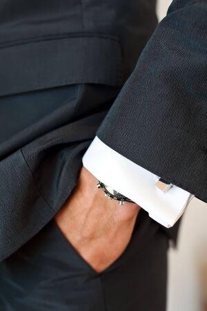 punos: Primer plano de la mano de un hombre en el bolsillo de traje que llevaba un reloj y un brazalete-enlace en la camisa. Foto de archivo