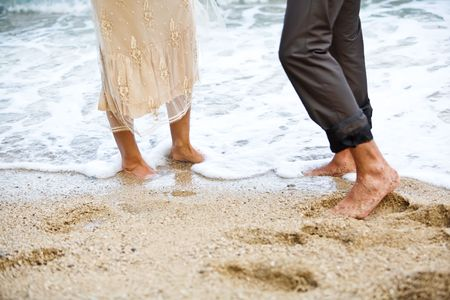 bare women: Wedding couples feet in the water on the beach. Stock Photo