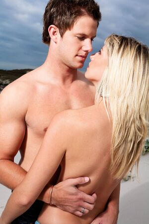 Goodlooking young couple topless on the beach. Stock Photo - 6544322