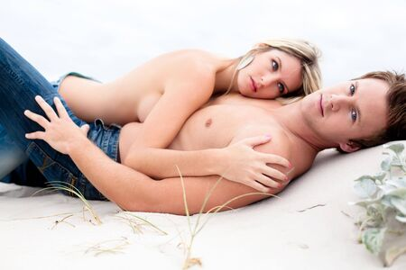 Goodlooking young couple lying down topless on the beach.