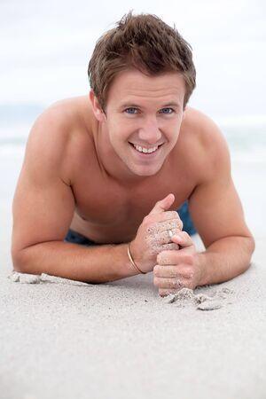 seins nus: Homme heureux sur la plage aux seins nus dans le sable.