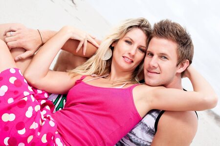 Attractive young couple sitting on the beach. photo