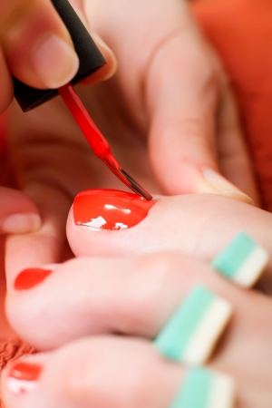 Closeup of a womans toes being painted with red nail polish. photo