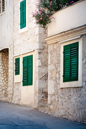 Croatian house with green shutters covering the windows photo