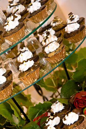 Cupcakes on a glass display at a wedding. photo