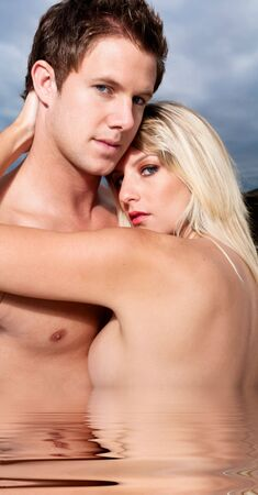 Goodlooking young couple topless on the beach. Stock Photo